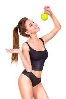 Спорт женщины держа зеленое яблоко и усмехаясь на белизне изолированный. здоровая еда и образ жизни концепция.