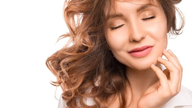Женщина с закрытыми глазами, изолированные на белой стене. касаясь кожи лица вручную. концепция естественной красоты и ухода за кожей