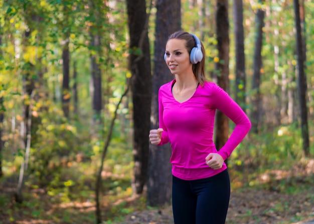 健康的なライフスタイルのコンセプトです。森でジョギングし、ヘッドフォンで音楽を聴く女性。