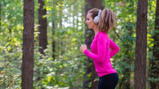 森でジョギングし、ヘッドフォンで音楽を聴く女性。側面図。
