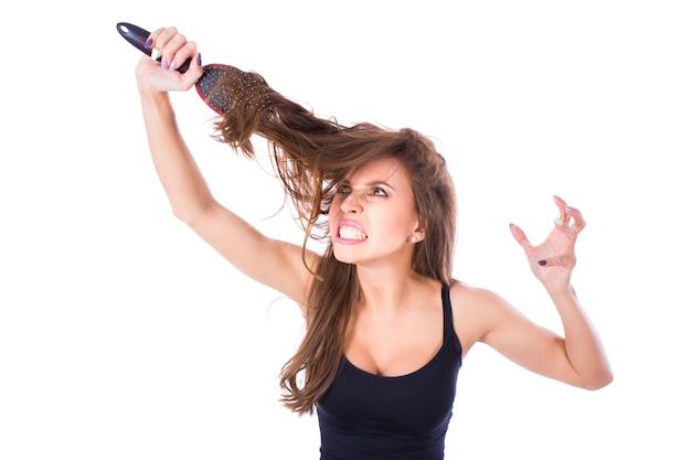 髪の中に問題がある美しい少女。孤立したスタジオ撮影
