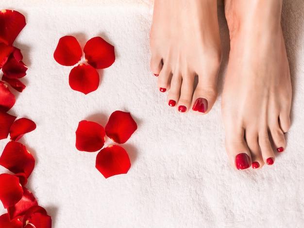 スパとウェルネス。テリー織りのタオルの上にバラの花びらを持つ女性の足。