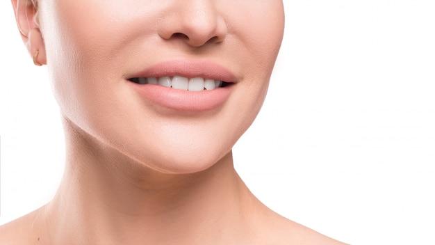 女性の笑顔のビューを閉じます。歯科のコンセプトです。白い壁に分離されたビューを閉じます。