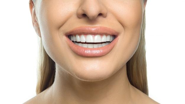 女性の笑顔の写真をクローズアップ。歯科のコンセプトです。白い壁に分離されました。