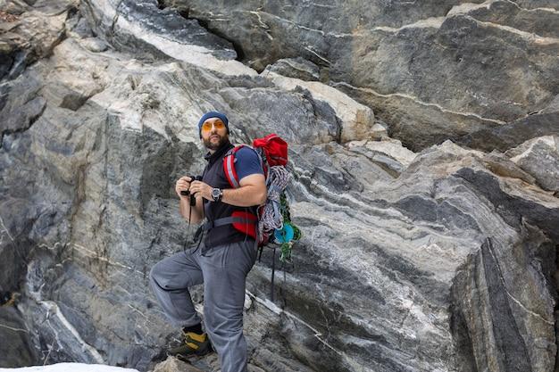Человек турист с рюкзаком стоит возле отвесной каменной скалы.