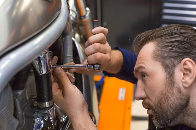 機械ワークショップで何かを修正する男の写真