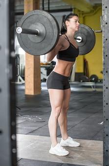 女性の写真をクローズアップは、ジムでバーベルでワークアウトしながら体重を持ち上げています。健康的なライフスタイルのコンセプトです。