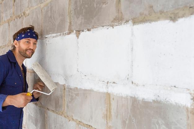 Человек красит стену. строитель в рабочей форме.