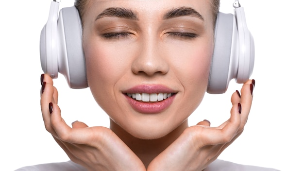 ヘッドフォンで音楽を聴く若い女性のビューを閉じます。
