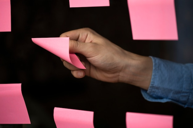 ボードから付箋のピンクの紙のメモを引き裂く男性の腕のクローズアップ
