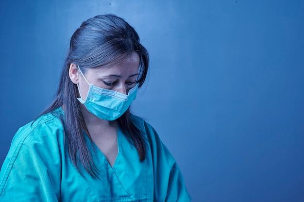 Измученная медсестра закрывает глаза