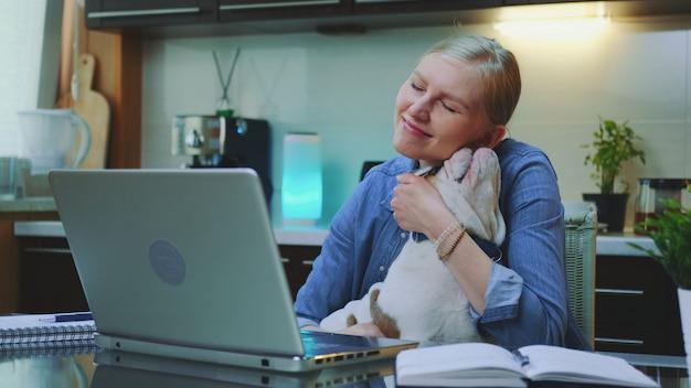 Улыбающаяся женщина, поглаживающая и обнимающая бульдога, сидя за компьютером