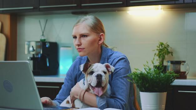 Крупным планом жизнерадостная женщина обнимает маленькую собаку на кухне