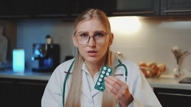 Видеозвонок пациенту. женщина-врач в медицинском халате, объясняя, как принимать лекарства