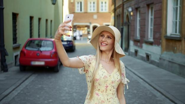 Женщина, принимая селфи на улице