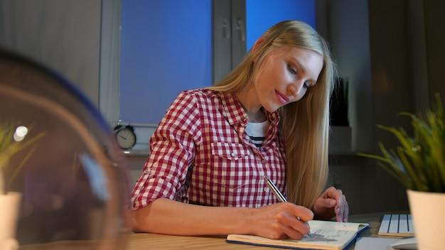 Веселая женщина, пишущая в ежедневнике