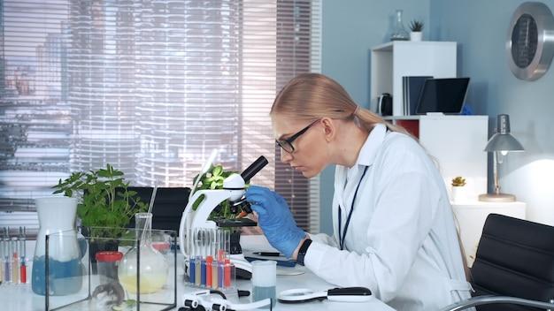 Женщина-ученый с помощью пипетки, чтобы бросить образец на слайде