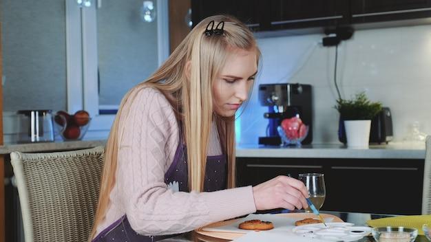 Милая молодая женщина учя украсить пряники дома