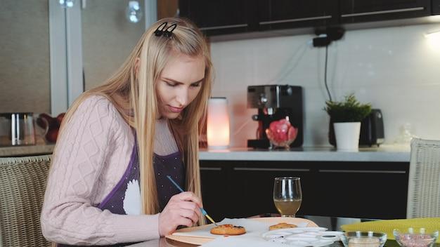 Жизнерадостная женщина практикует в отделке пряников на кухне у себя дома