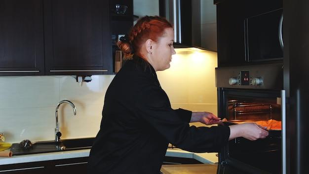 Пекарня кладет в духовку противень с печеньем