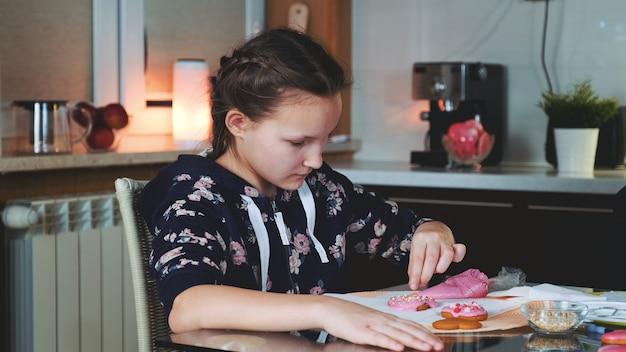 陽気な若い女の子が彼女の母親が休日のお祝いのクッキーを飾るのを助ける