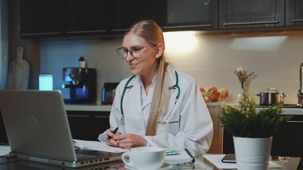 自宅から患者にビデオ通話を行う医療ガウンの女医