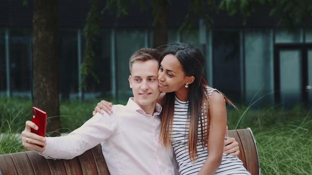 Романтическая пара многонациональное, сидя на скамейке в парке и принимая селфи