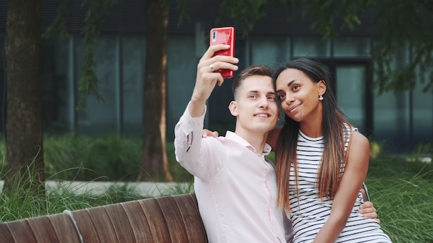 Веселая молодая пара, принимая селфи, сидя на скамейке на открытом воздухе