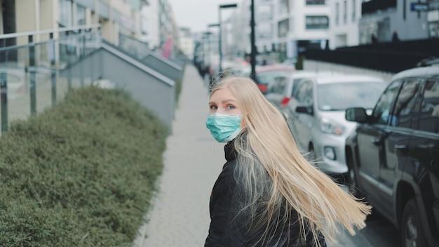 Молодая блондинка в медицинской маске, спасаясь от кого-то на улице.