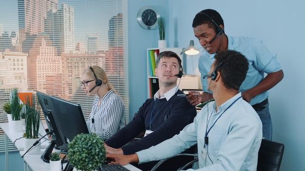 クライアントに電話しながら同僚に冗談を言う多民族のカスタマーサービス担当者