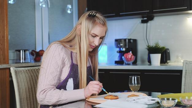 Окрашивание сладкого печенья специальными пищевыми красками на кухне.