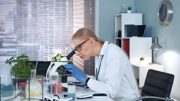 В современной исследовательской лаборатории: женщина-ученая с помощью пипетки бросает образец на предметное стекло