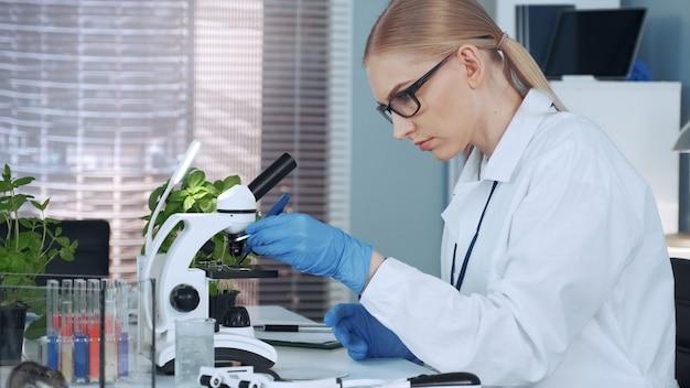 Преподаватель химии женского пола с помощью пинцета наносит органический материал на предметное стекло и смотрит под микроскоп