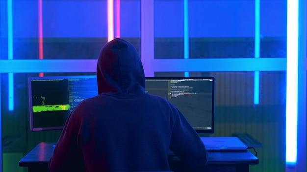 ハッカープログラムを書いて、黒いジャケットと頭にフードを被ったハッカーの背面図