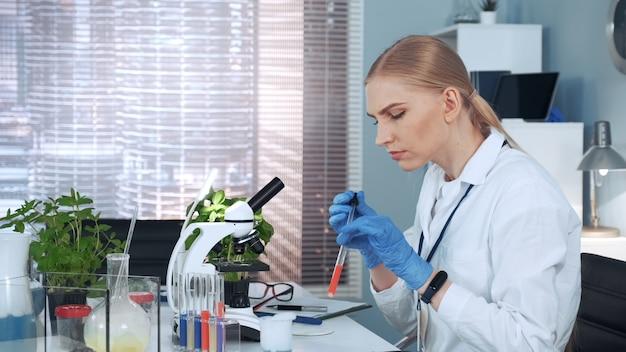 Женщина-ученый бросает образец на предметное стекло микроскопа и изучает его