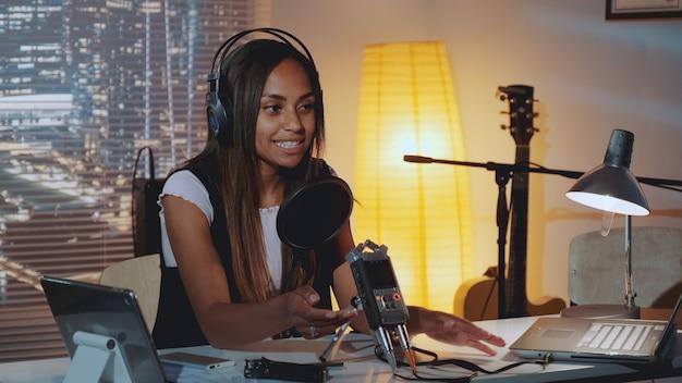 ホームスタジオで彼女の朝のスピーチを録音する女性のラジオニュースレポーターのクローズアップ
