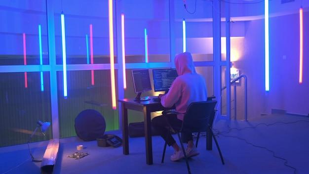 ハッカーの作業場所:色付きのネオンのある部屋で作業するハッカー