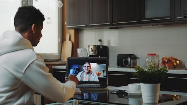 Темнокожий мужчина делает видео-консультацию с врачом на компьютере