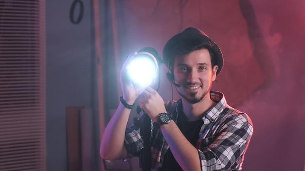 カメラにランプを向けて笑顔を始めるキーグリップの拡大図。