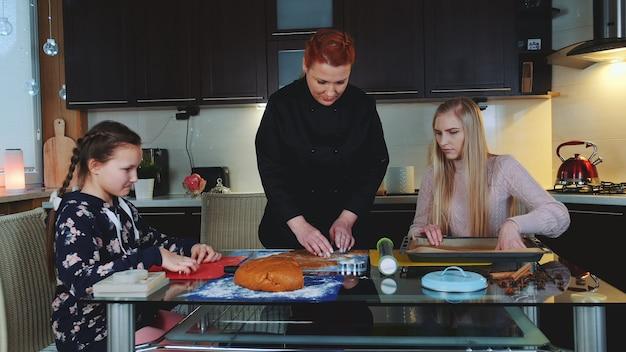 Женщины пекут пряники на кухне дома