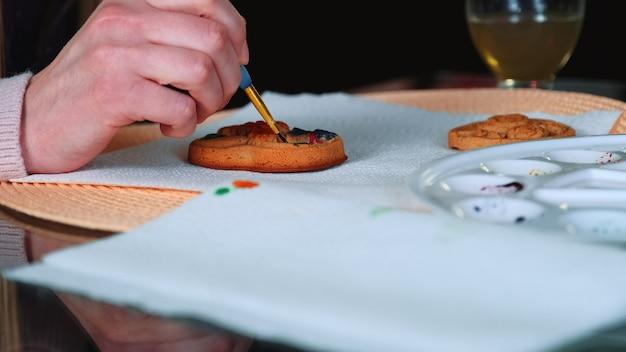 Съемка крупным планом женских рук, рисующих пряник на кухне