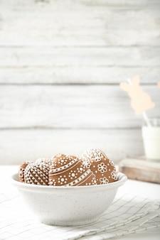 Пасхальное печенье на тарелку с стакан молока на фоне деревянные. пасхальные кролики.