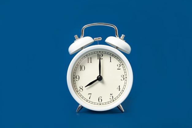 青色の背景に白い目覚まし時計。テキストのための場所