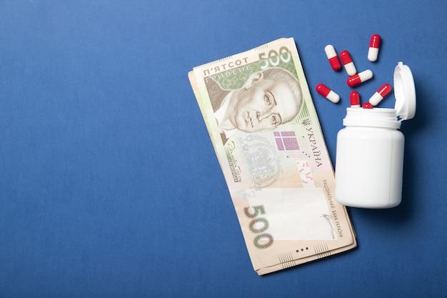 青色の背景に錠剤の瓶。医学と健康の概念。より高い薬価。政治と健康。ウクライナグリブナ