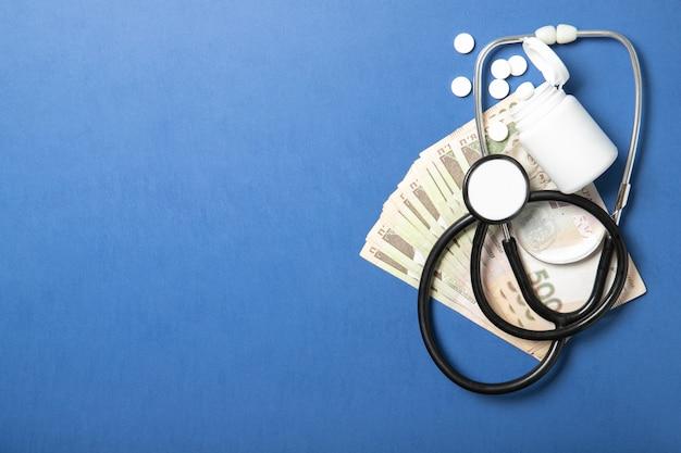 薬と青色の背景に聴診器の瓶。医学と健康の概念。より高い薬価。ポリシーと健康