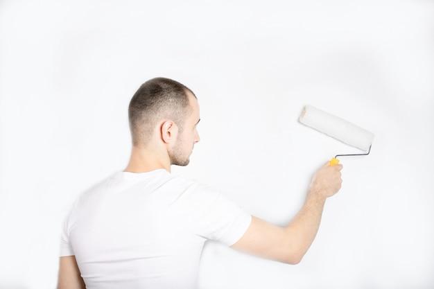 Парень красит стену строительным валиком.