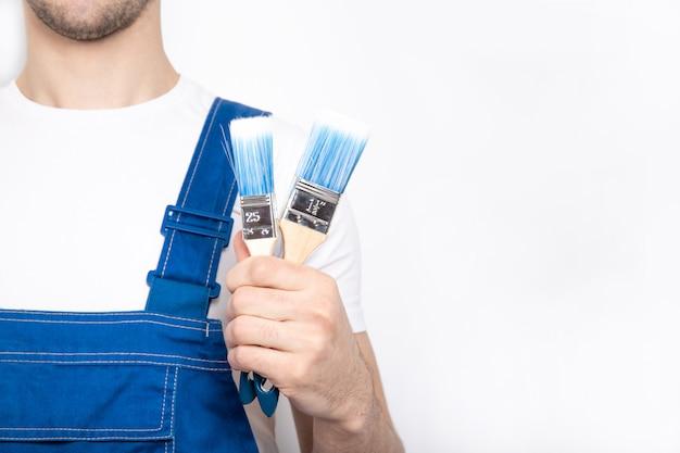 Молодой парень в синем комбинезоне держит строительную кисть в руке.