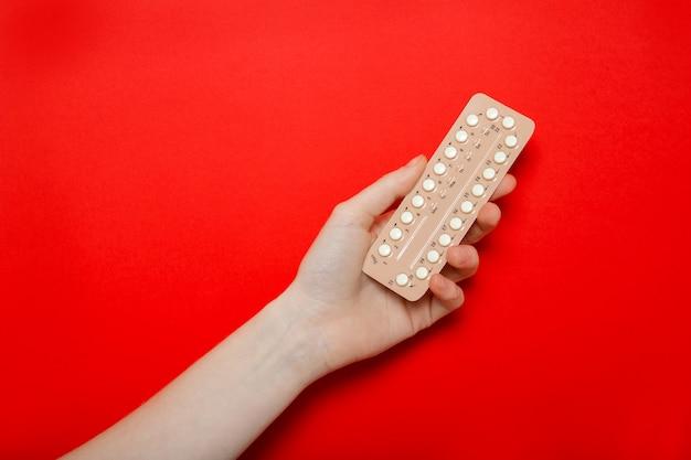 女の子は彼女の手で避妊薬を保持しています。避妊。赤い壁、テキストのための場所。