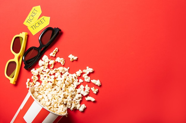 Бумажный стаканчик с попкорном на красном фоне. очки и билеты в кино