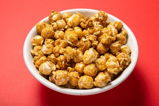 Тарелка с карамельным попкорном на красном фоне